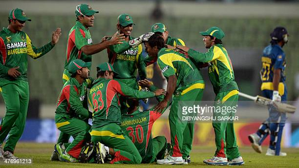 Bangladeshi cricketers congratulate bowler Rubel Hossain after he ran out Sri Lankan batsman Mahela Jayawardene during the tenth match of the Asia...
