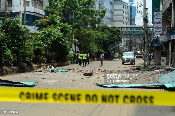 Bangladeshi crime scene investigators collect evidence from a street after part of a hotel building collapsed following a raid on a militant hideout...