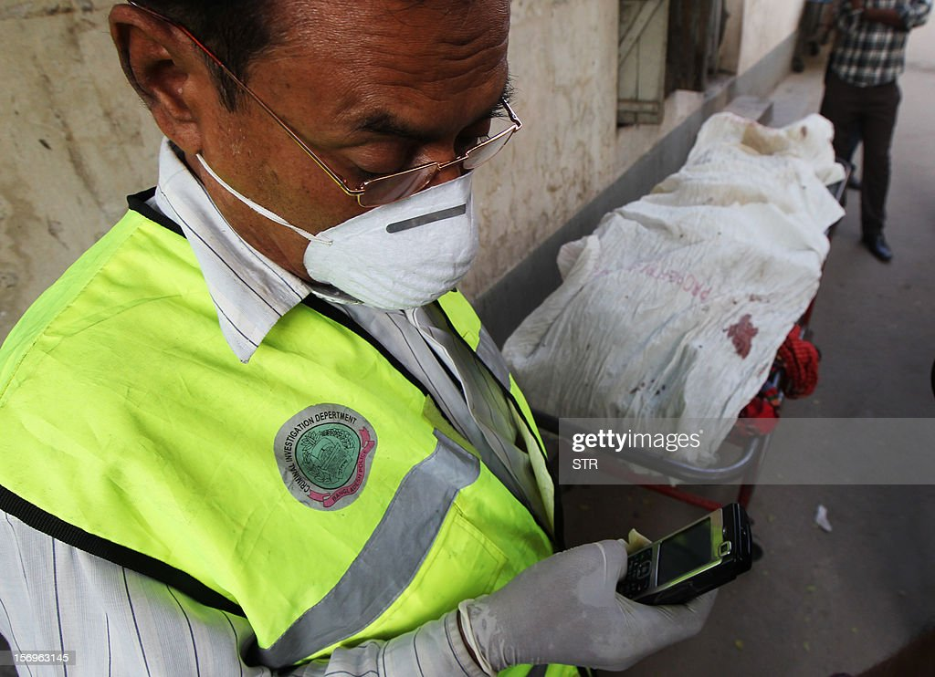 A Bangladeshi Criminal Investigation Department employee checks his cell phone near the remains of victims, from a garment factory that burned down, before taking them to a lab for forensic testing at the Dhaka Medical College Hospital in Dhaka on November 26, 2012. Garment workers staged mass protests to demand the end to 'deathtrap' labour conditions after Bangladesh's worst-ever textile factory fire, as a new blaze sparked fresh panic and terror. Ahead of the first of a series of mass funerals for the 110 victims, survivors of Saturday night's blaze joined several thousand colleagues to block a highway and march in the manufacturing hub of Ashulia.
