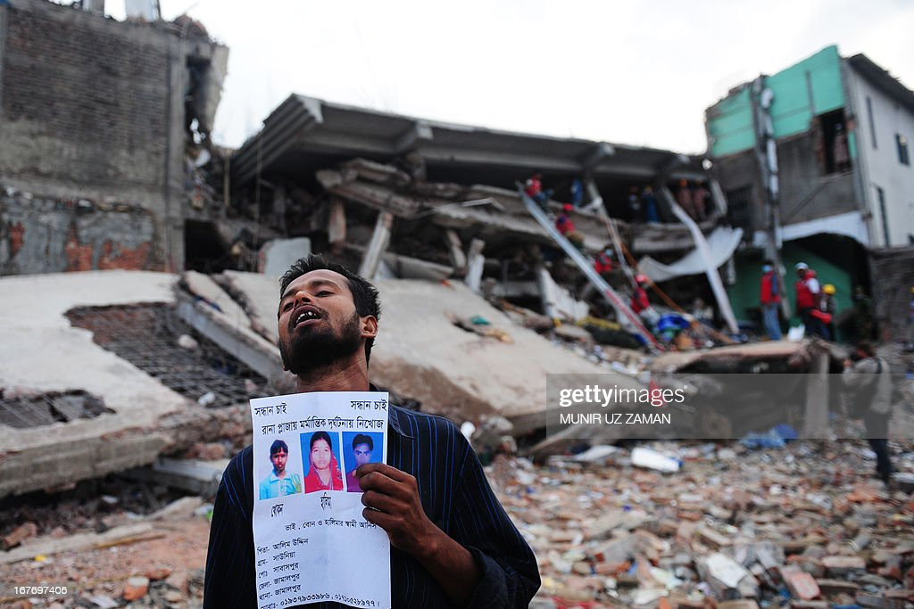 A Bangladeshi family member holds a portrait of his missing relatives, believed trapped in the rubble of an eight-storey building that collapsed in Savar, on the outskirts of Dhaka, on April 28, 2013. Four people were hauled out alive overnight more than 90 hours after the disaster, but the last feeble cries for help, still audible from inside the mountain of rubble early in the day, appeared to have ended. Rescue teams at the site of a collapsed factory block in Bangladesh where 363 people have died called in heavy-lifting equipment as hopes of finding more survivors faded. AFP PHOTO/ Munir uz ZAMAN