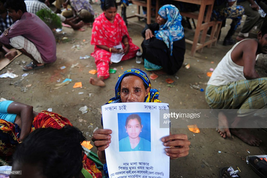 A Bangladeshi family member holds up the portrait of her missing relative, believed to be trapped in the rubble of an eight-storey building collapse in Savar, on the outskirts of Dhaka, on April 29, 2013. Thousands of Bangladeshi garment workers walked out of their factories Monday, demanding the death penalty for the owner of a tower block that collapsed and killed at least 381 of their colleagues. AFP PHOTO/MUNIR UZ ZAMAN