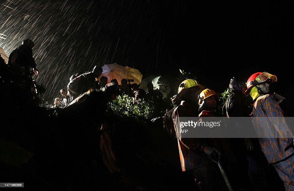 Bangladeshi fire fighters look on after a landslide in Chittagong on June 27, 2012. Nearly 90 people have been killed in landslides in southeast Bangladesh after three days of rains that triggered flash floods and severed transport links, officials said.