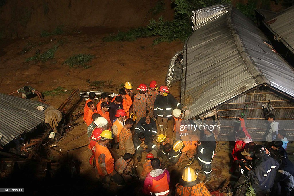 Bangladeshi fire fighters try to retrieve a dead body after a landslide in Chittagong on June 27, 2012. More than 55 people have been killed in landslides in southeast Bangladesh after three days of rains that triggered flash floods and severed transport links, officials said.