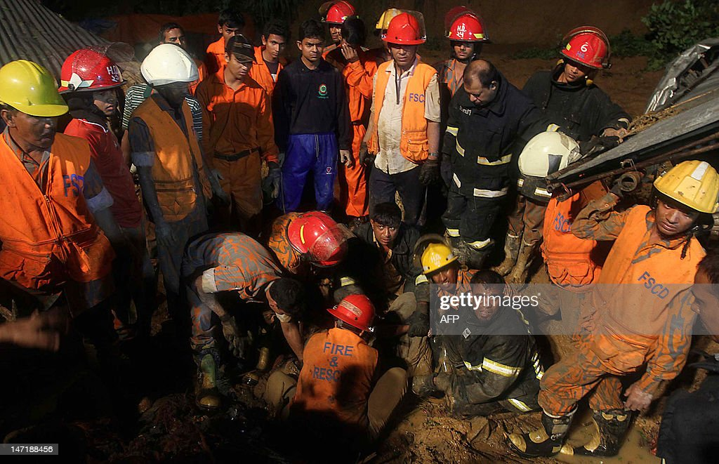 Bangladeshi fire fighters try to retrieve a dead body after a landslide in Chittagong on June 27, 2012. Nearly 90 people have been killed in landslides in southeast Bangladesh after three days of rains that triggered flash floods and severed transport links, officials said. AFP PHOTO/ STR