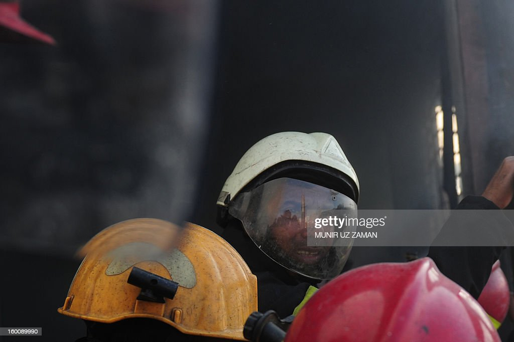 A Bangladeshi firefighter looks on as he and others attempt to extinguish a blaze at a garment factory in Dhaka on January 26, 2013. At least six workers at a garment factory in the Bangladeshi capital were killed in a stampede as a fire broke out. AFP PHOTO/Munir uz ZAMAN