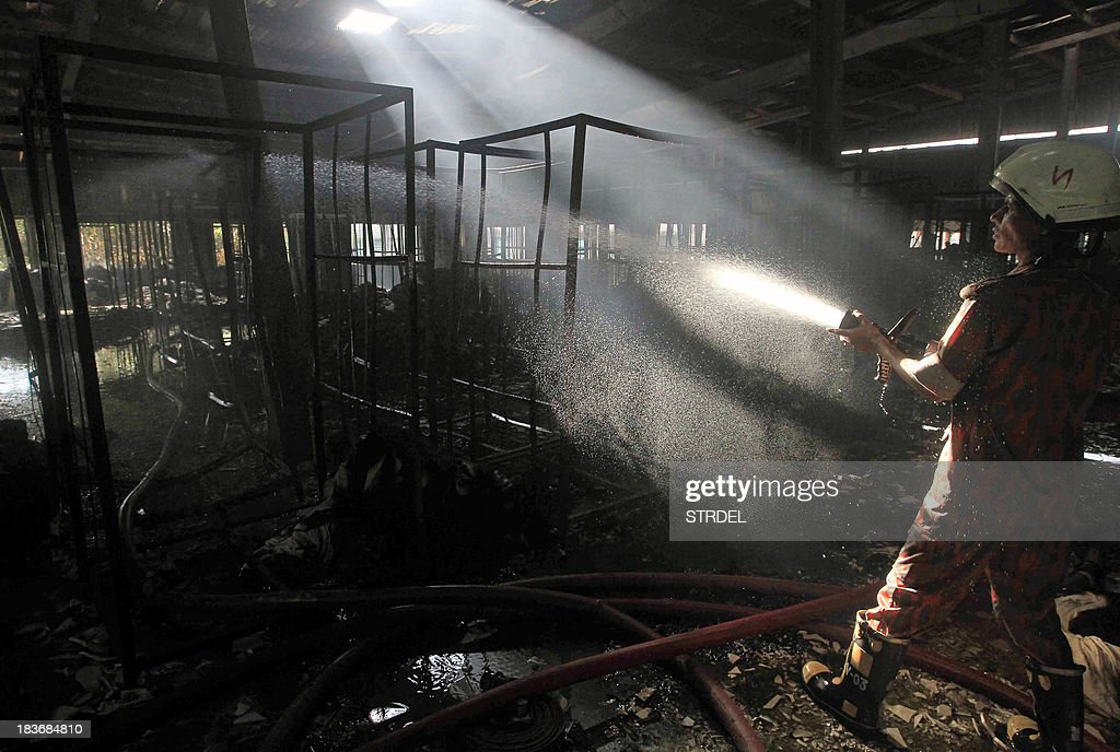 A Bangladeshi firefighter works at the scene following a blaze that engulfed a garment factory in Sripur on October 9, 2013. A huge fire at a Bangladeshi factory where workers were making clothes for labels such as Gap and H&M has killed seven people in the latest disaster to blight the country's garment industry.