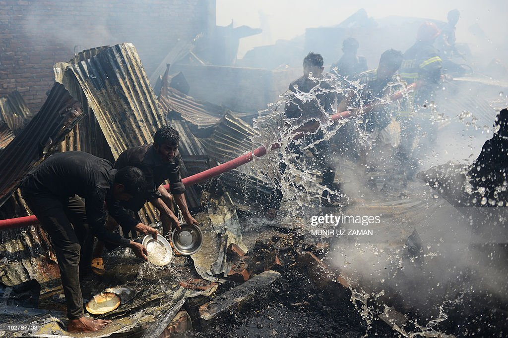 Bangladeshi firefighters and residents try to control a blaze at a slum in Dhaka on February 27, 2013. At least 300 shanties were gutted in the Kallyanpur's Natun Bazar slum fire in Dhaka, but no casualties took place, police said. AFP PHOTO/ Munir uz ZANAN