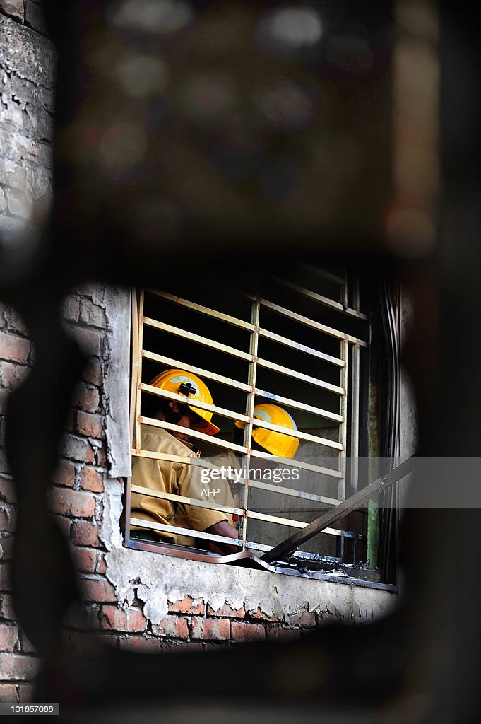 Bangladeshi firefighters are seen through a burnt window in Old Dhaka on June 6, 2010. Bangladeshi firefighters said June 4 an illegal chemical warehouse caught fire and exploded, fueling a toxic blaze that ripped through one of Dhaka's most densely populated areas, killing over 110 people.