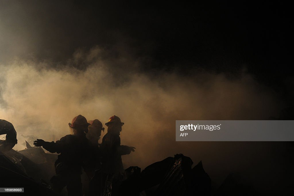 Bangladeshi firefighters attempt to extinguish a blaze at a market in Dhaka on April 7, 2013. More then 100 shops burnt as a blaze tore through a market at the middle of the night. AFP PHOTO/Munir uz ZAMAN
