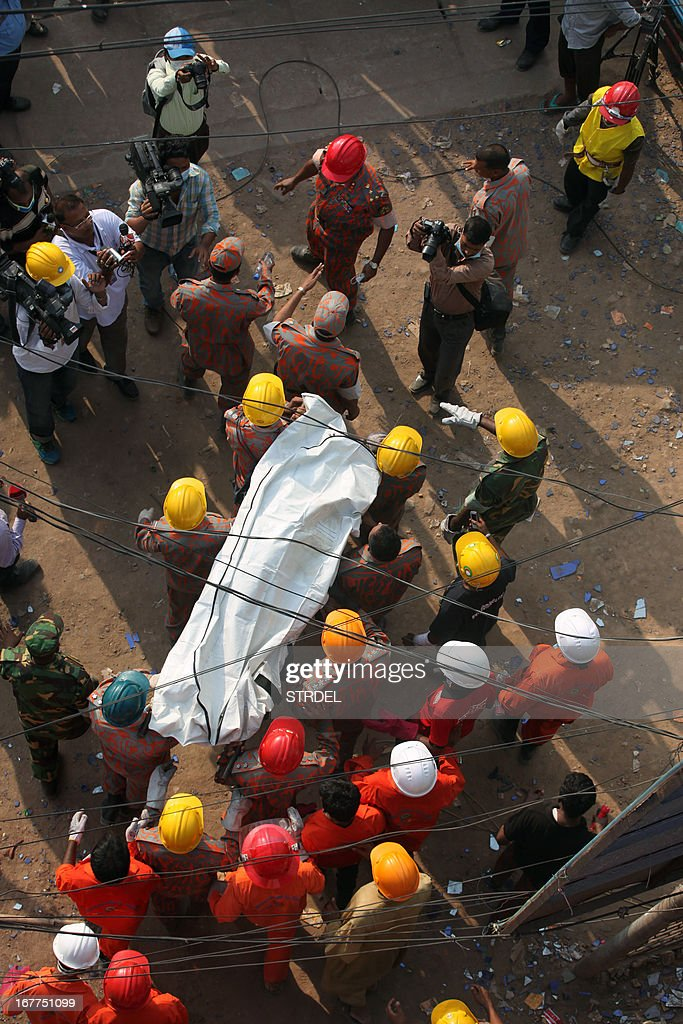 Bangladeshi firefighters carry the body of garment worker Shahana following her unsuccessful rescue from the eight-storey building that collapsed in Savar, on the outskirts of Dhaka on April 29, 2013. A blaze broke out in the wreckage of a Bangladesh factory block April 28, killing a woman whose 110-hour battle for survival had touched the nation following its worst industrial disaster, the country's fire chief said. AFP PHOTO/STR