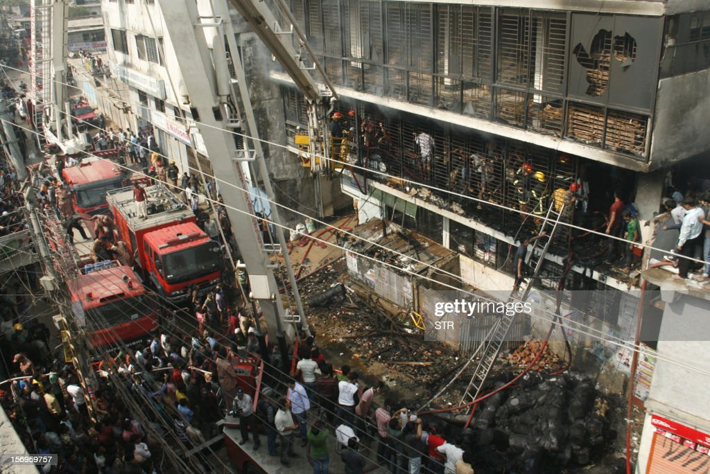Bangladeshi firefighters stand in a burned out bulding as they try and control a fire that broke out at a garment factory on the outskirts of Dhaka on November 26, 2012. Bangladesh firefighters quelled a new blaze at a garment factory as the country mourned the death of 110 workers in a weekend blaze at an apparel plant, the export industry's worst-ever accident. The latest fire caused widespread damage at the plant on the outskirts of the capital Dhaka, but no casualties were reported after rescue teams searched the building for workers feared to have suffocated in toxic black fumes.