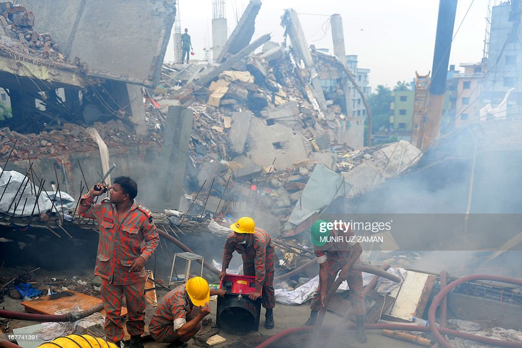 Bangladeshi fire-fighters try to control a blaze after a fire broke out during a rescue attempt of a woman as Bangladeshi Army personel begin the second phase of the rescue operation using heavy equipment after an eight-storey building collapsed in Savar, on the outskirts of Dhaka, on April 29, 2013. Thousands of Bangladeshi garment workers walked out of their factories Monday, demanding the death penalty for the owner of a tower block that collapsed and killed at least 381 of their colleagues. AFP PHOTO/MUNIR UZ ZAMAN