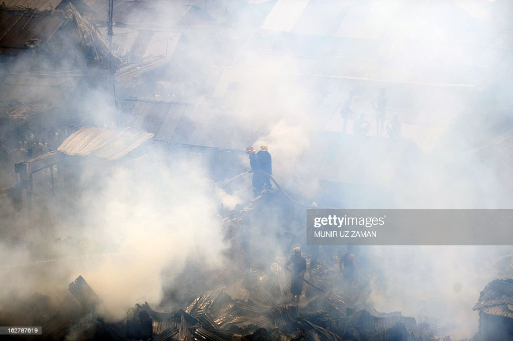 Bangladeshi firefighters try to control a blaze at a slum in Dhaka on February 27, 2013. At least 300 shanties were gutted in the Kallyanpur's Natun Bazar slum fire in Dhaka, but no casualties took place, police said. AFP PHOTO/Munir uz ZANAN
