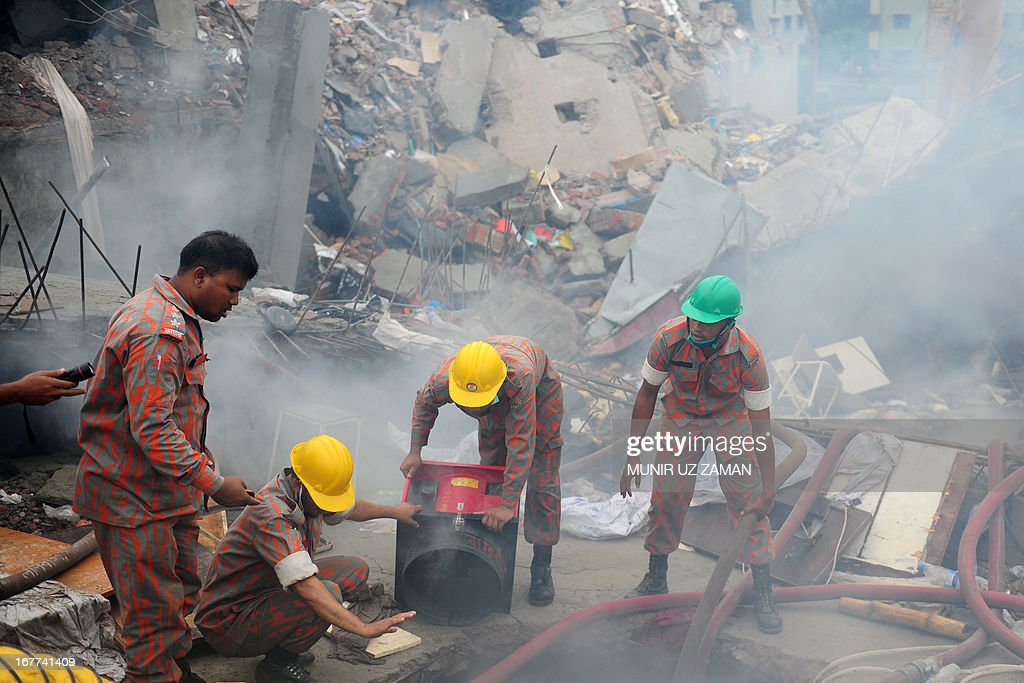 Bangladeshi fire-fighters try to control a blaze following a fire during a rescue attempt of a woman as Bangladeshi Army personel begin the second phase of the rescue operation using heavy equipment after an eight-storey building collapsed in Savar, on the outskirts of Dhaka, on April 29, 2013. Thousands of Bangladeshi garment workers walked out of their factories Monday, demanding the death penalty for the owner of a tower block that collapsed and killed at least 381 of their colleagues.