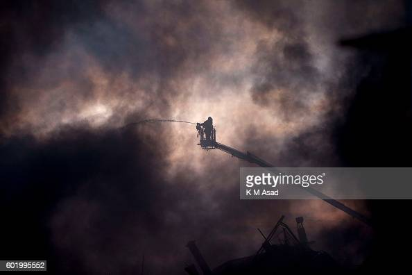 Bangladeshi firefighters try to douse flames middle in the smoke after an explosion made a factory in Tongi Official said at least 23 people were...