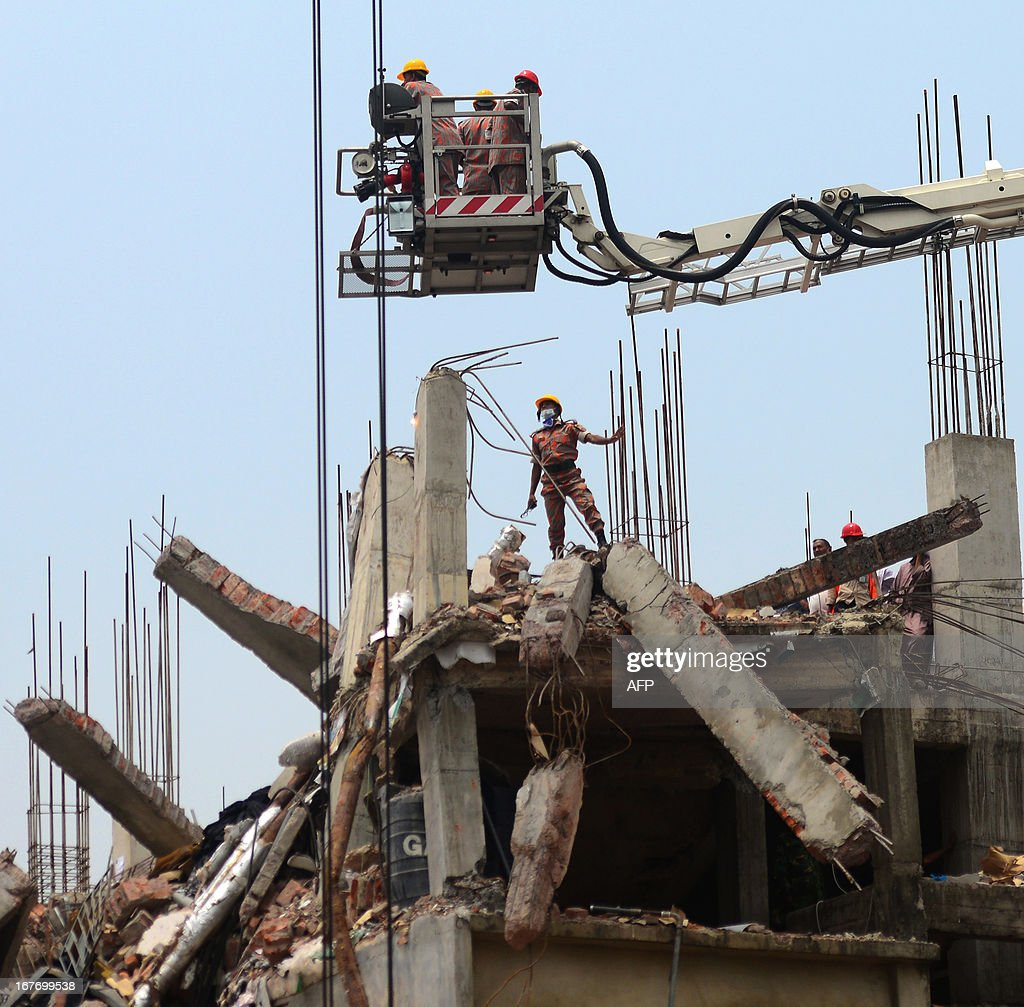 Bangladeshi firefighters use a crane to inspect the roof of an eight-storey building that collapsed in Savar, on the outskirts of Dhaka on April 28, 2013. Four people were hauled out alive overnight more than 90 hours after the disaster, but the last feeble cries for help, still audible from inside the mountain of rubble early in the day, appeared to have ended. Rescue teams at the site of a collapsed factory block in Bangladesh where 363 people have died called in heavy-lifting equipment as hopes of finding more survivors faded. AFP PHOTO/ Munir uz ZAMAN