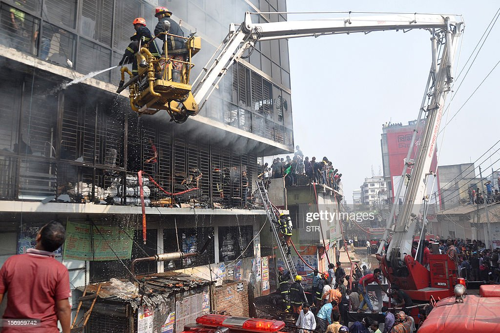 Bangladeshi firefighters use a water cannon on a crane to try and control a fire that broke out at a garment factory on the outskirts of Dhaka on November 26, 2012. Bangladesh firefighters quelled a new blaze at a garment factory as the country mourned the death of 110 workers in a weekend blaze at an apparel plant, the export industry's worst-ever accident. The latest fire caused widespread damage at the plant on the outskirts of the capital Dhaka, but no casualties were reported after rescue teams searched the building for workers feared to have suffocated in toxic black fumes.