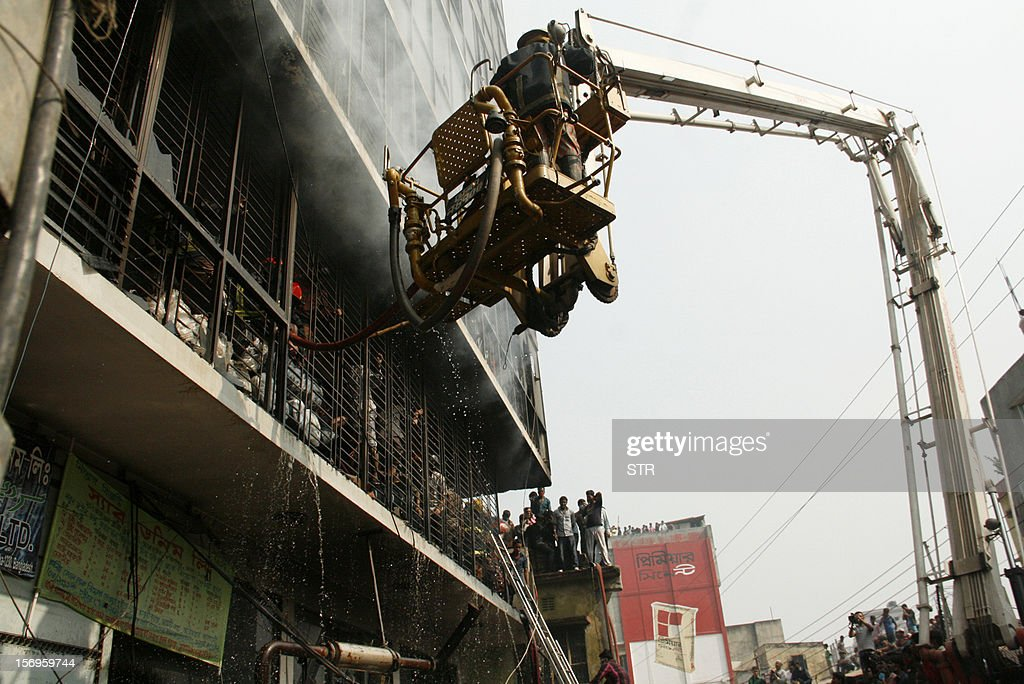 Bangladeshi firefighters use a water cannon on a crane to try and control a fire that broke out at a garment factory on the outskirts of Dhaka on November 26, 2012. Bangladesh firefighters quelled a new blaze at a garment factory as the country mourned the death of 110 workers in a weekend blaze at an apparel plant, the export industry's worst-ever accident. The latest fire caused widespread damage at the plant on the outskirts of the capital Dhaka, but no casualties were reported after rescue teams searched the building for workers feared to have suffocated in toxic black fumes. AFP PHOTO/ STR