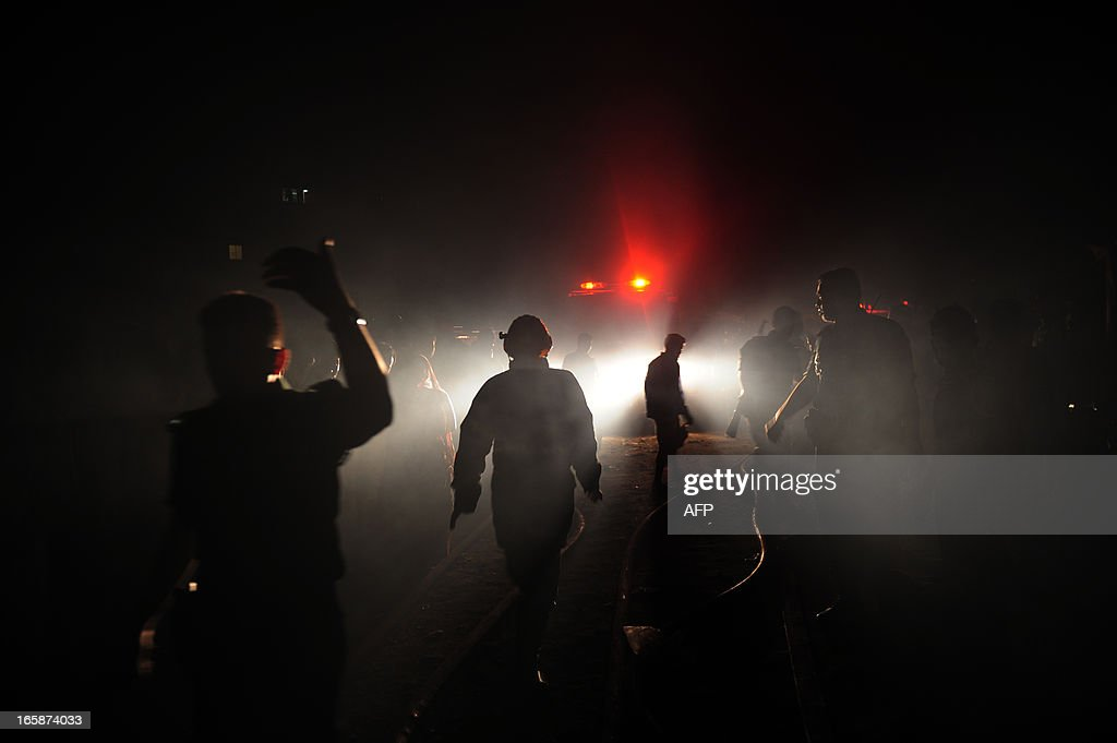 Bangladeshi firefighters walk past lights as they attempt to extinguish a blaze at a market in Dhaka on April 7, 2013. More then 100 shops were raized after a fire raced through a market in the middle of the night. AFP PHOTO/Munir uz ZAMAN
