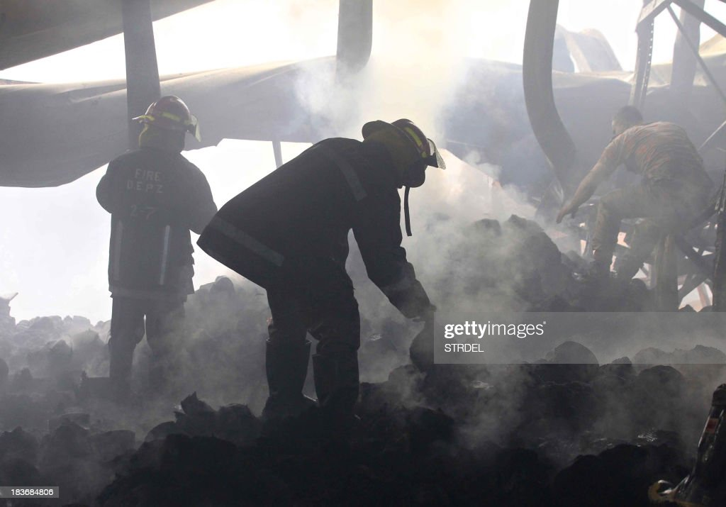 Bangladeshi firefighters work at the scene following a blaze that engulfed a garment factory in Sripur on October 9, 2013. A huge fire at a Bangladeshi factory where workers were making clothes for labels such as Gap and H&M has killed seven people in the latest disaster to blight the country's garment industry.