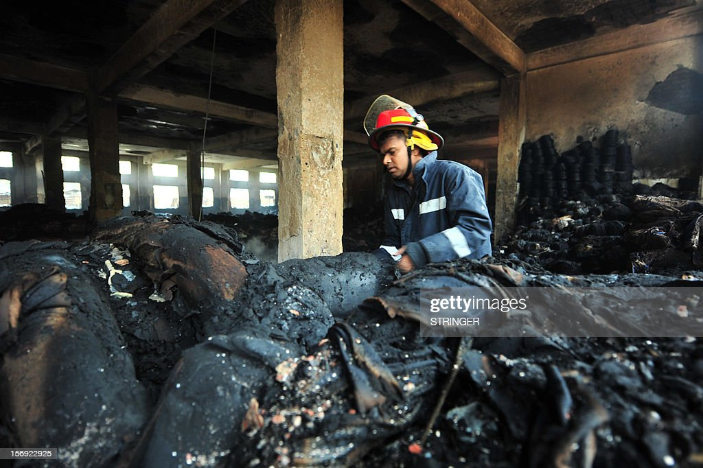 A Bangladeshi fire-man examines burnt materials after a fire in the nine-storey Tazreen Fashion plant in Savar, about 30 kilometres north of Dhaka on November 25, 2012. Rescue workers in Bangladesh recovered 109 bodies on Sunday after a fire tore through a garment factory, forcing many workers to jump from high windows to escape the smoke and flames.