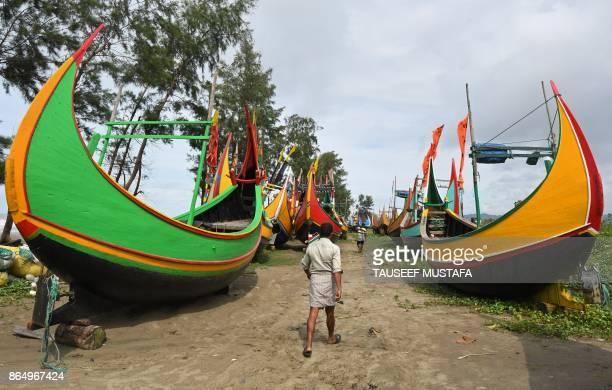 Bangladeshi fisherman walks near fishing boats at Maheshkali pora island near Teknaf on October 22 2017 Thousands of Rohingya Muslims stranded near...