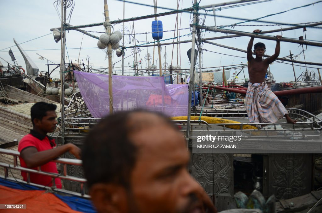 Bangladeshi fishermen tie up their vessels in the harbour of Chittagong on May 15, 2013 during preparations for the expected arrival of Cyclone Mahasen. Cyclone Mahasen is moving northeastwards over the Bay of Bengal and expected to make landfall on May 17 morning north of the Bangladeshi city of Chittagong, sparing Myanmar's restive Rakhine state from its full fury, the UN said. AFP PHOTO/ Munir uz ZAMAN
