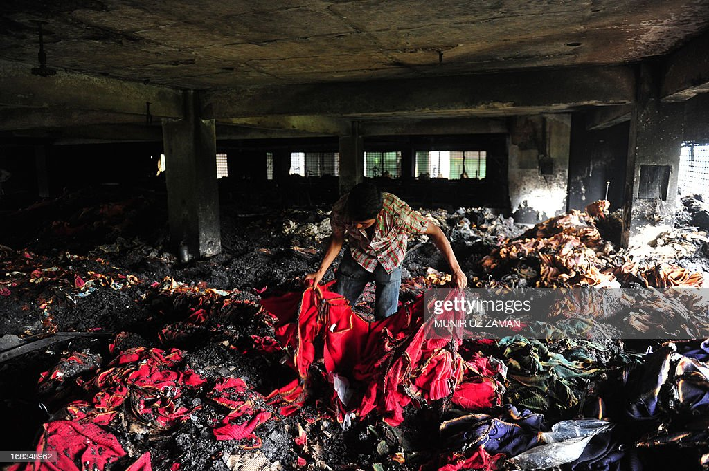 A Bangladeshi garment worker holds up burnt cloth inside a gutted factory in Dhaka on May 9, 2013. A fire at a garment factory killed at least eight people May 9 in the latest disaster to hit Bangladesh's textile industry, still reeling from the deaths of more than 900 people in a building collapse. AFP PHOTO/Munir uz ZAMAN