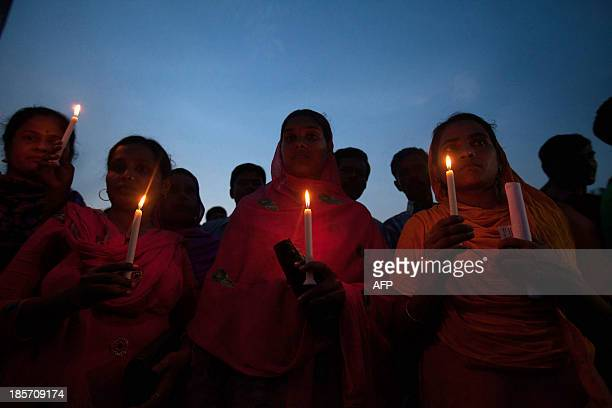Bangladeshi garment workers and relatives of victims of the Rana Plaza building collapse hold candles during a memorial at the site of the Rana Plaza...
