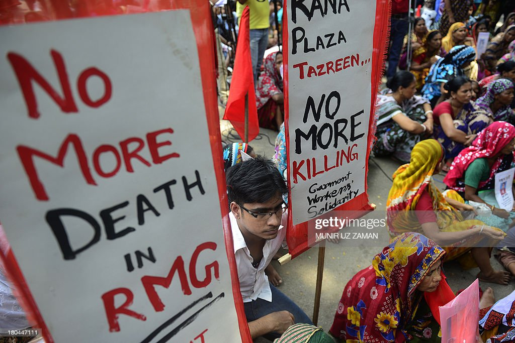 Bangladeshi garment workers hold placards during a protest on wages and compensation in Dhaka on September 13, 2013. Hundreds of workers took part in the protest to demand a minimum monthly wage 8000 taka (103 USD) and compensation for the victims and injured of the Rana Plaza building collapse of April 24. AFP PHOTO/Munir uz ZAMAN