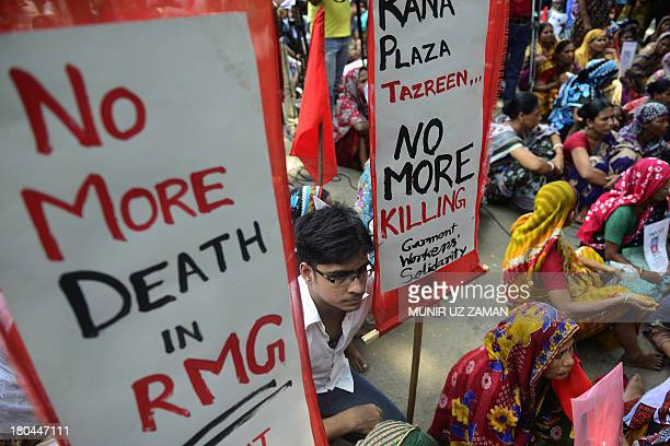 Bangladeshi garment workers hold placards during a protest on wages and compensation in Dhaka on September 13 2013 Hundreds of workers took part in...