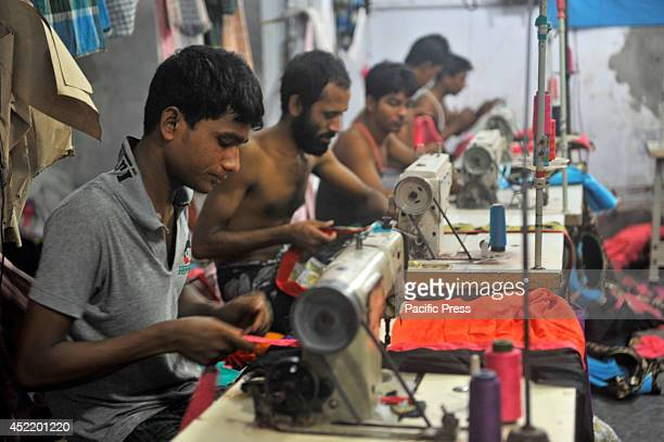 Bangladeshi garment workers sewing clothes in a factory for the domestic market in Keranigonj in Dhaka Some garment factories located near Buriganga...