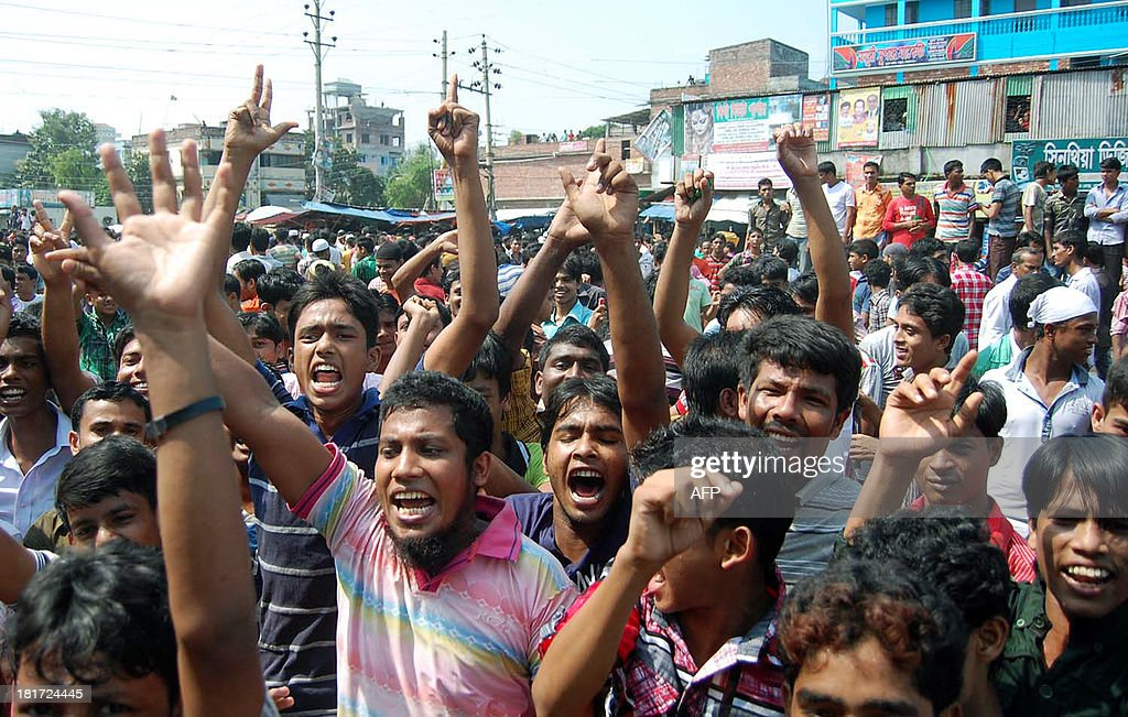 Bangladeshi garment workers shout slogans during a protest in Narayanganj on September 24, 2013. Angry Bangladeshi garment workers blocked roads, set factories alight and clashed with police for a third day on Monday as protests demanding a minimum monthly wage of USD100 spread outside the capital.
