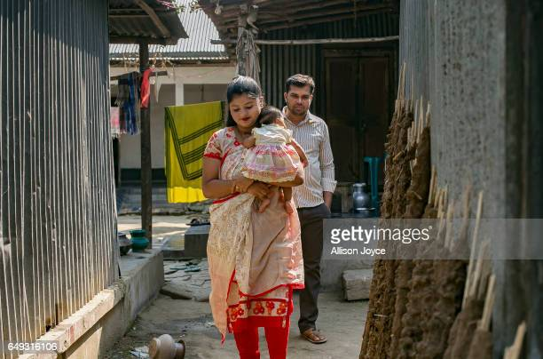 Meghla walks with her baby and her husband Liton on March 7 2017 in Khulna division Bangladesh 17yearold Meghla married her 30yearold husband Liton...
