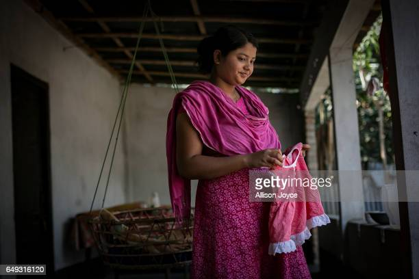 Meghla holds her daughters dress on March 7 2017 in Khulna division Bangladesh 17yearold Meghla married her 30yearold husband Liton during an...