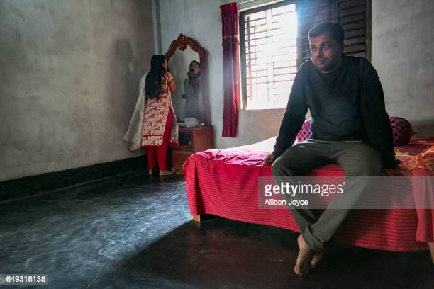 Meghla does her makeup while her husband Liton sits on the bed on March 7 2017 in Khulna division Bangladesh 17yearold Meghla married her 30yearold...