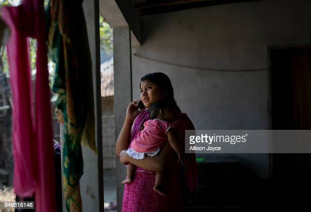 Meghla talks on the phone as she holds her 2 month old baby on March 7 2017 in Khulna division Bangladesh 17yearold Meghla married her 30yearold...