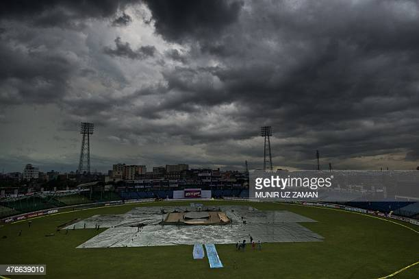 Bangladeshi ground staff cover the playing field as rain comes during the second day of the only cricket Test match between Bangladesh and India at...