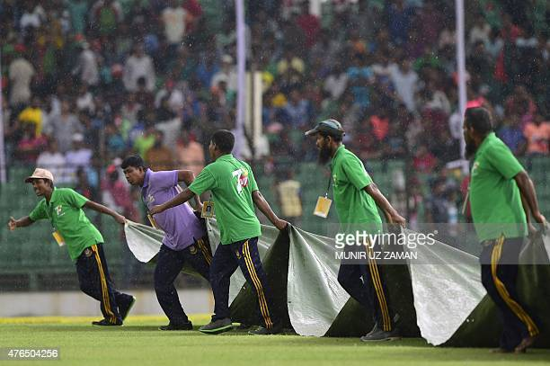 Bangladeshi groundstaff cover the playing field as rain stops play during the first day of the first cricket Test match between Bangladesh and India...