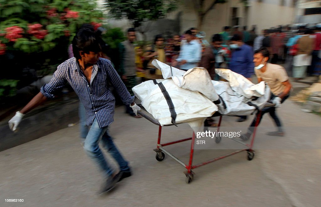 Bangladeshi health workers carry the remains of victims, from a garment factory that burned down, to a lab for forensic testing at the Dhaka Medical College Hospital in Dhaka on November 26, 2012. Garment workers staged mass protests to demand the end to 'deathtrap' labour conditions after Bangladesh's worst-ever textile factory fire, as a new blaze sparked fresh panic and terror. Ahead of the first of a series of mass funerals for the 110 victims, survivors of Saturday night's blaze joined several thousand colleagues to block a highway and march in the manufacturing hub of Ashulia. AFP PHOTO/ STR