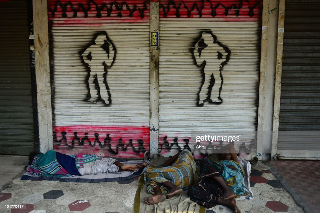 Bangladeshi homeless men sleep in front of a closed shop during a nationwide strike called by the opposition Bangladesh Nationalist Party (BNP) in protest against the detention of their leaders, in Dhaka on March 28, 2013. Schools and businesses were shut across Bangladesh on the second day of a general strike called by the country's main opposition party and Islamic allies. AFP PHOTO/Munir uz ZAMAN