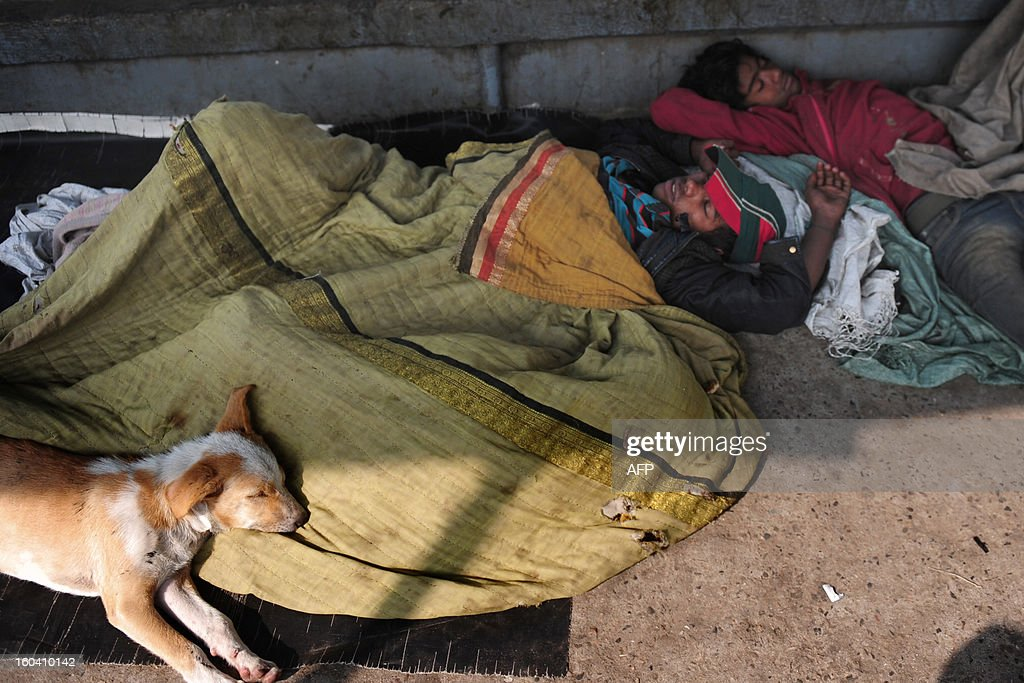 Bangladeshi homeless youth sleep with their pets in Dhaka on January 31, 2013. Bangladesh, one of the poorest countries in the world with a population of 150 million, counts on the inflow of foreign exchange from migrant workers to fund its imports. AFP PHOTO/ Munir uz ZAMAN