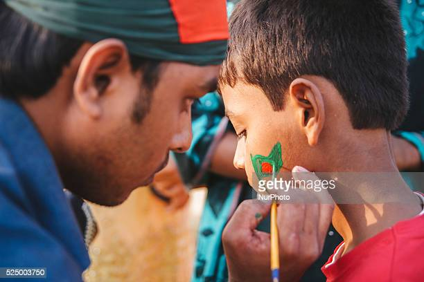 A Bangladeshi kid getting painting of Bangladesh's national flag on his face during a rally to mark the country's Victory Day in Dhaka on December 16...