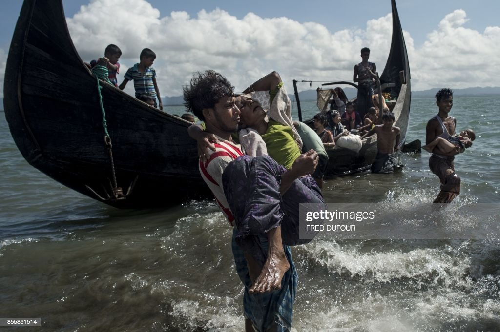 Bangladeshi man helps Rohingya Muslim refugees to disembark from a boat on the Bangladeshi shoreline of the Naf river after crossing the border from Myanmar in Teknaf on September 30, 2017. More than 2,000 Rohingya have massed along Myanmar's coast this week after trekking from inland villages in Rakhine state to join the refugee exodus to Bangladesh, state media reported September 30. They follow more than half a million fellow Rohingya who have emptied out of northern Rakhine in a single month, fleeing an army crackdown and communal violence the UN says amounts to 'ethnic cleansing'. /
