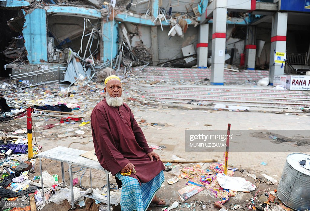 A Bangladeshi man looks on as he sits near the rubble of an eight-storey building that collapsed in Savar, on the outskirts of Dhaka, on April 28, 2013. Four people were hauled out alive overnight more than 90 hours after the disaster, but the last feeble cries for help, still audible from inside the mountain of rubble early in the day, appeared to have ended. Rescue teams at the site of a collapsed factory block in Bangladesh where 363 people have died called in heavy-lifting equipment as hopes of finding more survivors faded. AFP PHOTO/ Munir uz ZAMAN