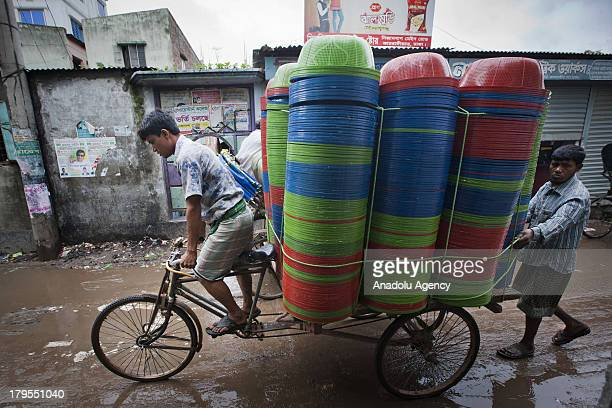 Bangladeshi man pulls plastic basins made from plastic waste in a bicycle trailer on May 30 2013 in Dhaka Bangladesh Recycling workers in Bangladesh...