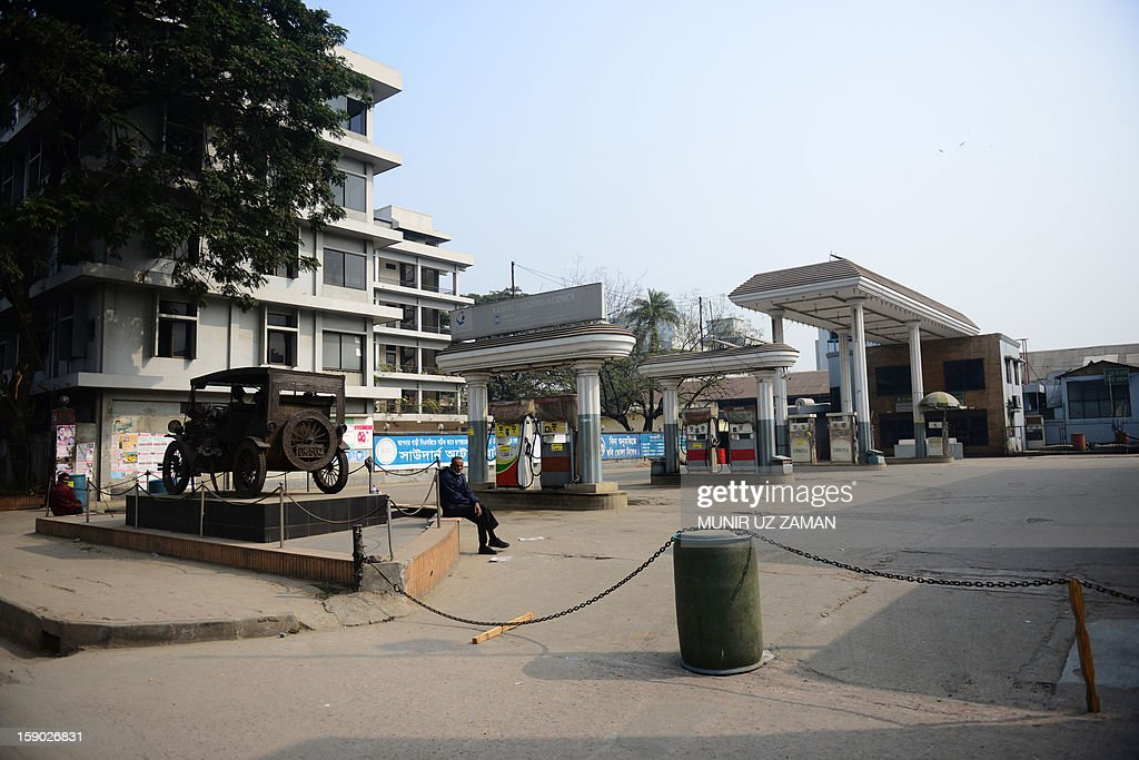 A Bangladeshi man sits inside a closed petrol station during a nationwide strike in Dhaka on January 6, 2013. Anti-government protesters set fire to cars and buses during the opposition alliance's day-long countrywide shutdown strike protesting the latest hike in fuel oil prices. AFP PHOTO/ Munir uz ZAMAN