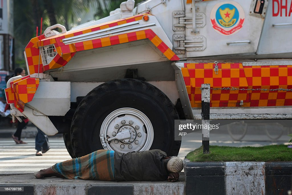A Bangladeshi man sleeps on a road divider as an armoured car passes during a nationwide strike called by the opposition Bangladesh Nationalist Party (BNP) in protest against the detention of their leaders, in Dhaka on March 27, 2013. The BNP and its allies enforced a 36 hours general strike across the country to mainly demand the release of more than 150 of their leaders and activists detained earlier this month. AFP PHOTO/Munir uz ZAMAN