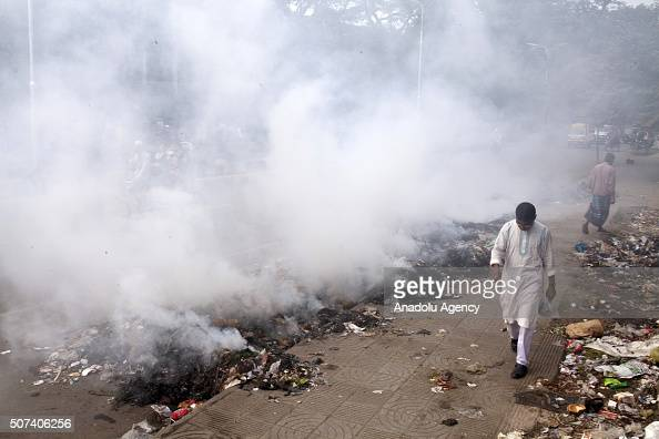 Bangladeshi man walks past smokes created by burning waste materials in a street in Dhaka Bangladesh on January 29 2016 The High Court on Monday...