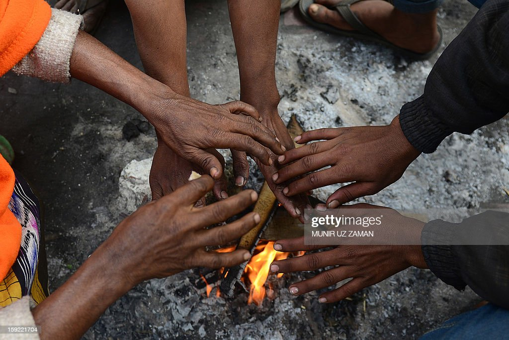 Bangladeshi men warm themselves around a bonfire on a cold day in Dhaka on January 10, 2013. Around 80 people have died in the past week due to cold related diseases such as pneumonia as mercury dropped to the lowest in tropical Bangladesh's history, officials said Thursday. Weather and Red Crescent Society officials said the toll was expected to grow as the cold wave that's been sweeping the country for the last week was set to linger two more days, affecting a quarter of the country's 153 million people. AFP PHOTO/Munir uz ZAMAN